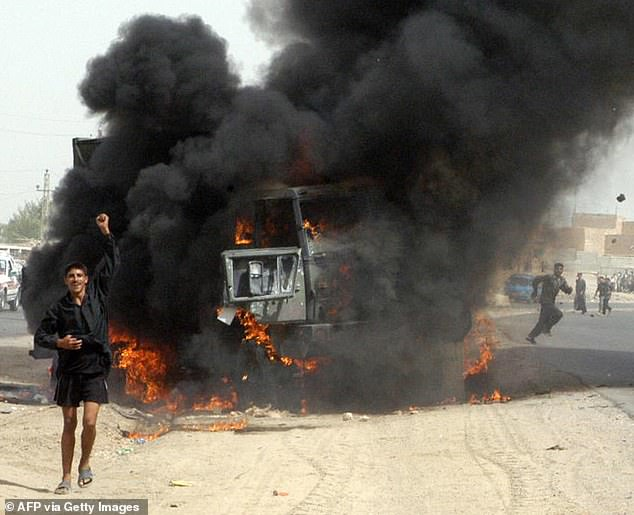 An Iraqi youth celebrates before a burning US army vehicle following an ambush on a US army convoy in the town of Khaldiyah, 80 kms west of Baghdad, 18 September 2003