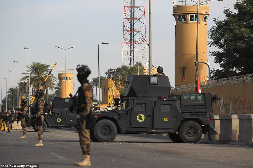 Iraqi security personnel defend the US embassy in Baghdad today, the walls of the complex are tarnished with scorch marks and graffiti