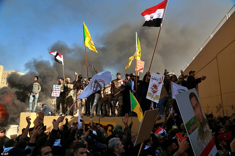 Protesters burned the property in front of the U.S. compound on Tuesday waving flags and banners for their specific groups in protest of the US airstrikes in Iraq on Sunday