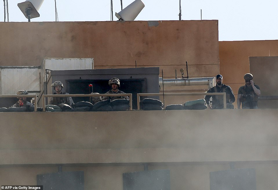 US soldiers watch from behind a smoke screen as Iraqi protesters surround the US embassy building in the capital Baghdad. They fired warning shots, followed by stun grenades and tear gas
