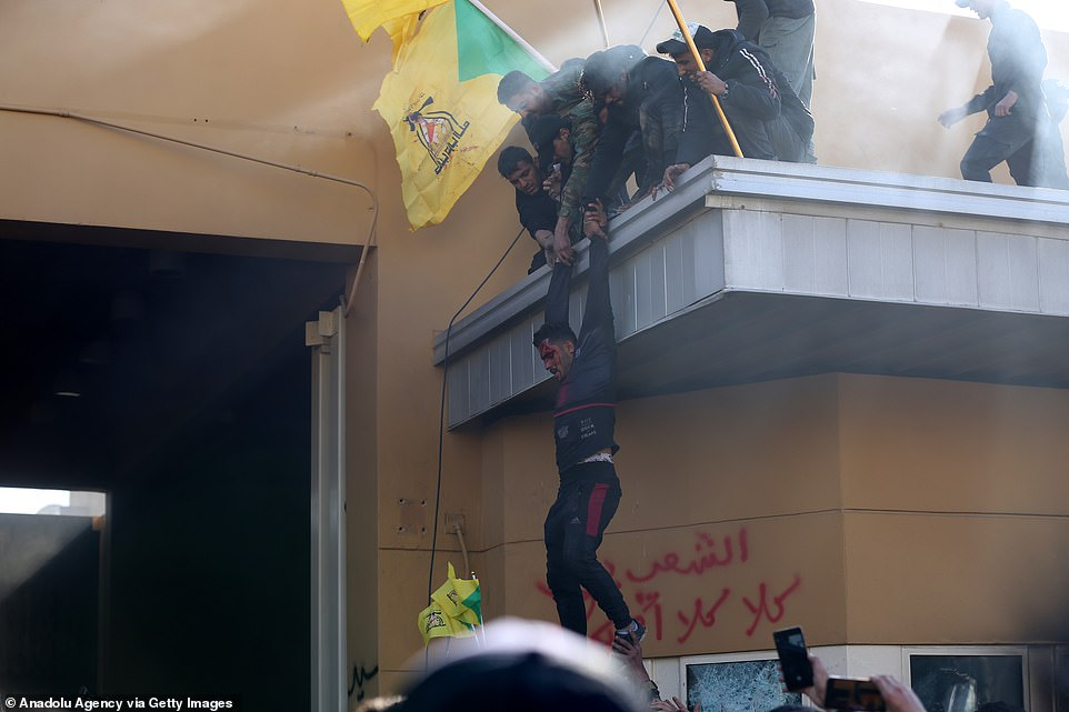 A wounded protester is seen held by pro-Iran militia members as chaos unfolds outside U.S. Embassy in Baghdad on Tuesday. The protester may have been wounded by American stun gun fire or in the tumult of the demonstrations