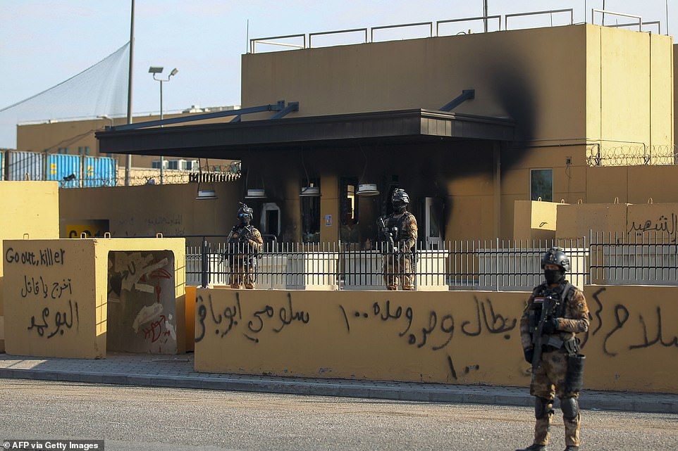 Iraqi counter-terror forces outside the scorched and spray-painted front of the US embassy in Baghdad on Thursday