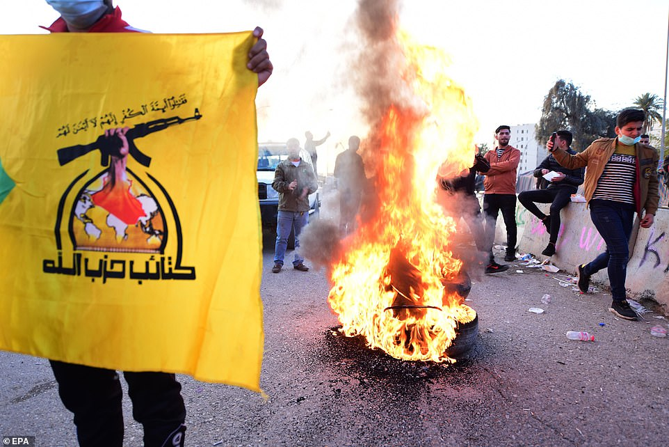 Members of Iran backed armed group Kataib Hezbollah (Hezbollah Brigades) set fire outside the U.S embassy inside the high security Green Zone area, in central Baghdad, Iraq on Wednesday