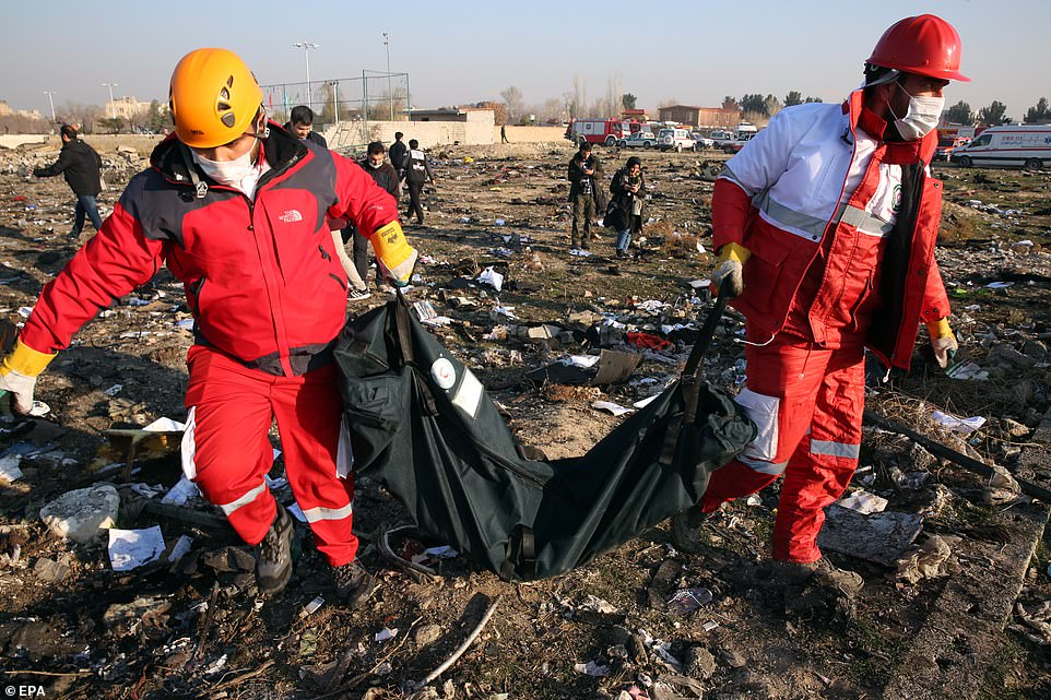 Members of the International Red Crescent collect bodies of victims around the wreckage near Tehran today