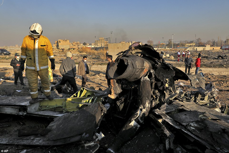 Rescue workers search the scene where a Ukrainian plane crashed in Shahedshahr in the early hours of Wednesday