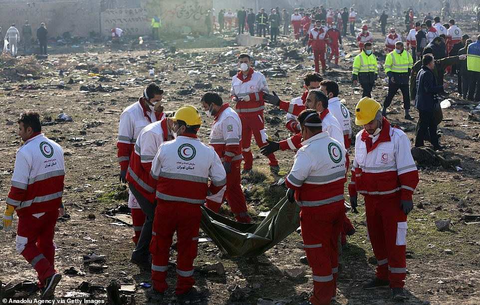 Rescuers carry a body bag at the crash site near Tehran today where 176 people were killed in the Ukrainian Airlines crash