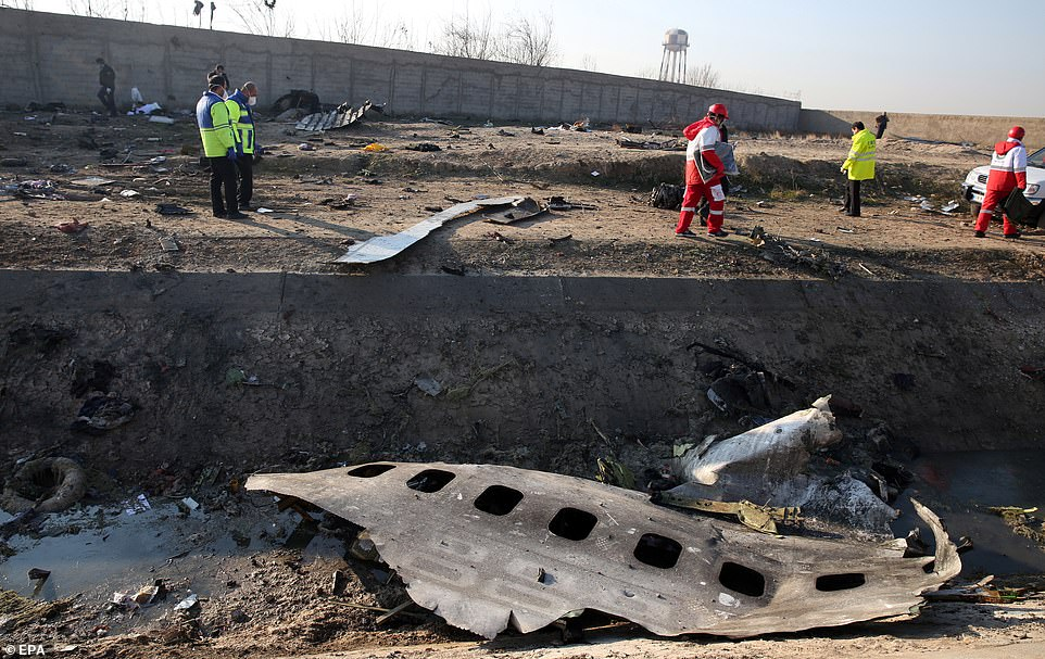 Emergency services personnel walk amidst the wreckage after an Ukraine International Airlines Boeing 737-800 carrying 176 people crashed