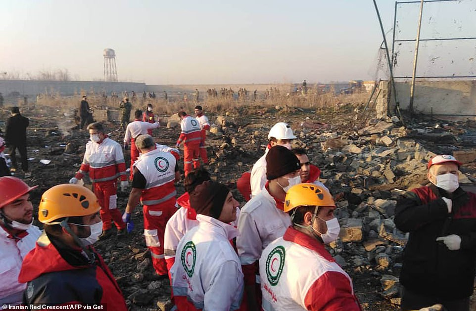 A handout picture provided by the Iranian Red Crescent shows rescue teams working at the crash site today