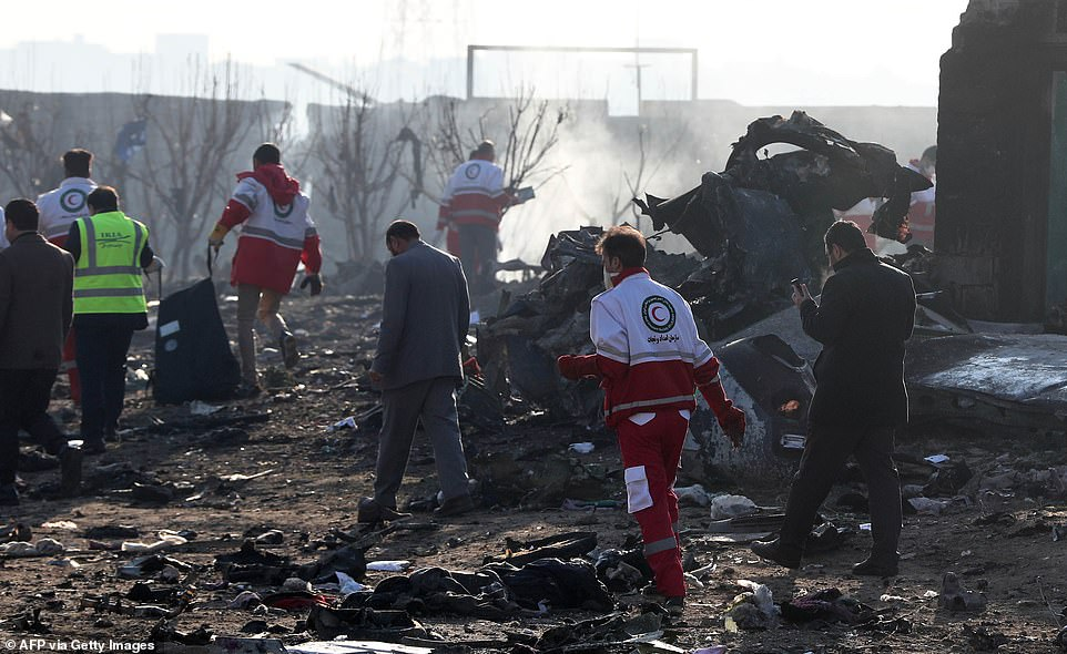 Rescue teams work amidst debris after a Ukrainian Airlines plane crashed just minutes into its journey